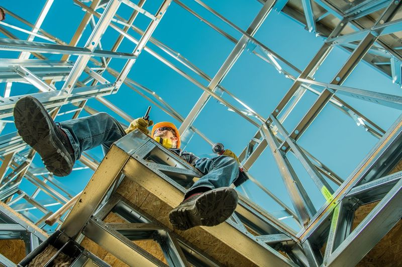 Low angle view of man sitting at construction site against sky