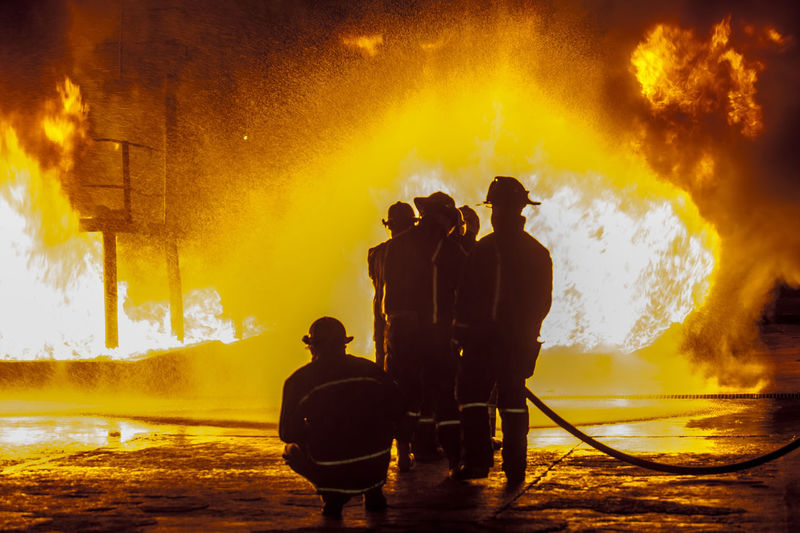 Firefighters spraying water on fire at night