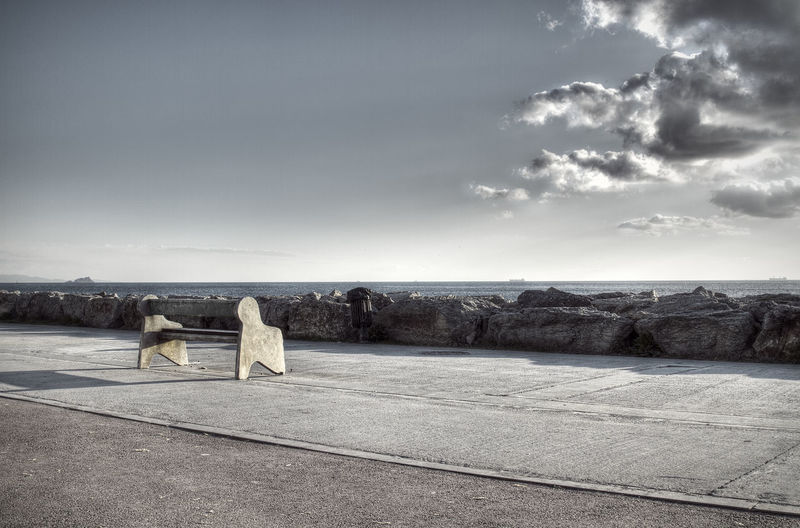 Empty Bench On Promenade By Sea Against Sky