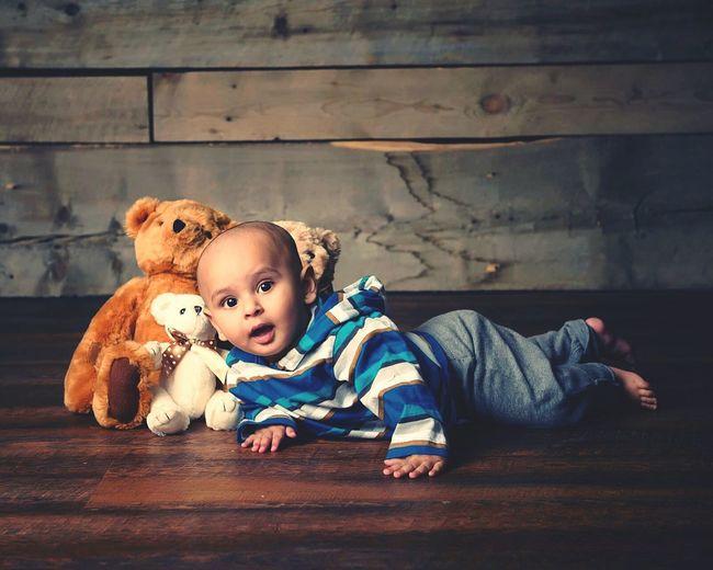 Side View Portrait Of Baby Boy Lying By Teddy Bears On Hardwood Floor
