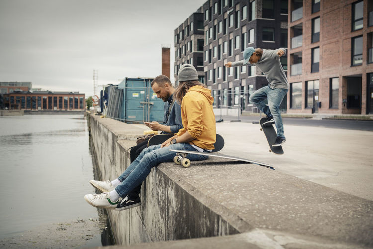 People on skateboard by canal in city against sky