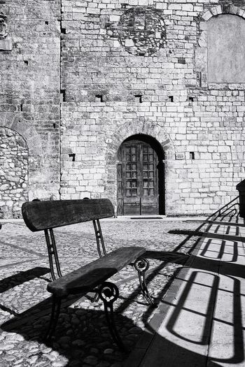 Empty bench against building wall
