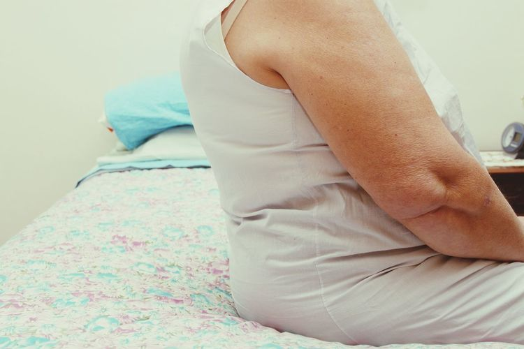 Midsection of woman relaxing on bed at home