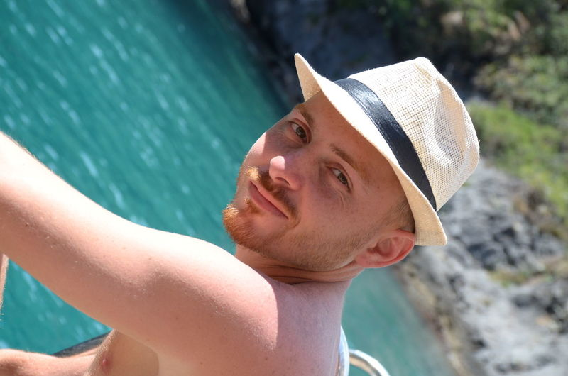 Close-up portrait of man wearing hat against sea
