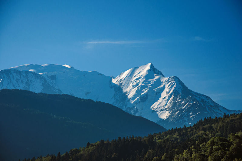 Alpine mountain landscape with forests and blue sky, near saint-gervais-les-bains, france.