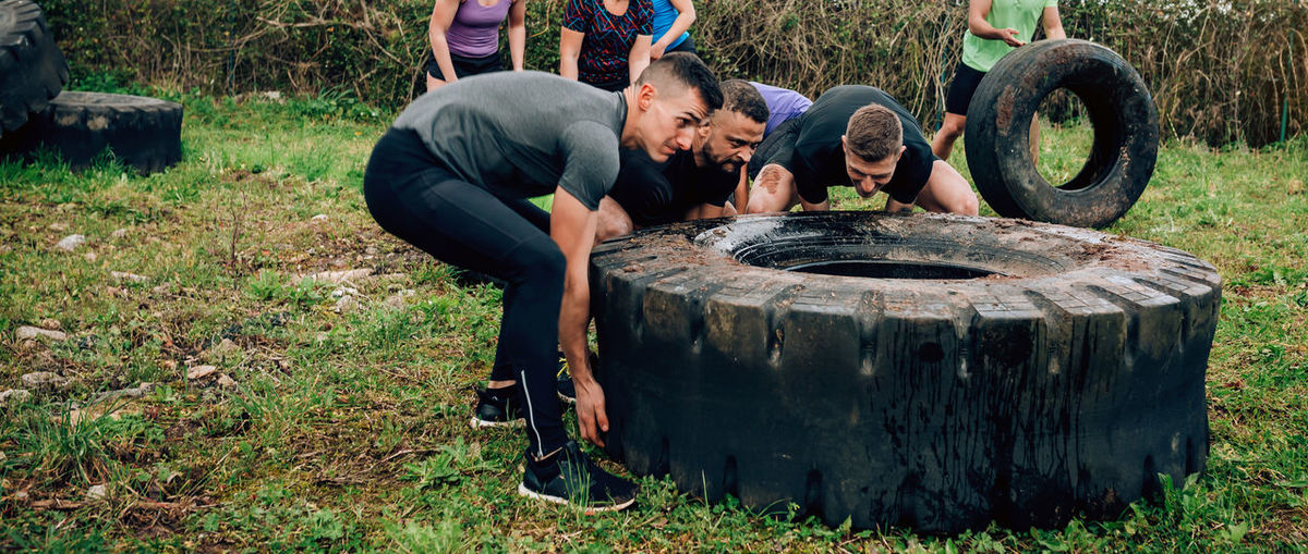 Group of participants in an obstacle course turning a truck wheel Obstacle Race Obstacle Course Ocr Collaboration Cooperation Runner Sport Horizontal Extreme Sports Outdoors Competition Training Workout Strong Effort Power Determination Team Turning Wheel Women Men Panorama Panoramic Banner