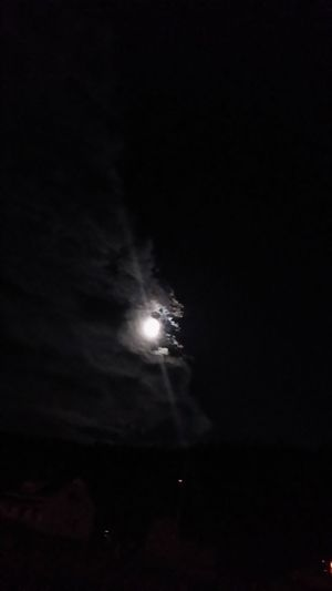 Low angle view of illuminated moon in sky at night