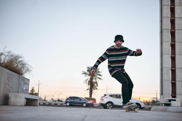 Young man skateboarding on skateboard against sky