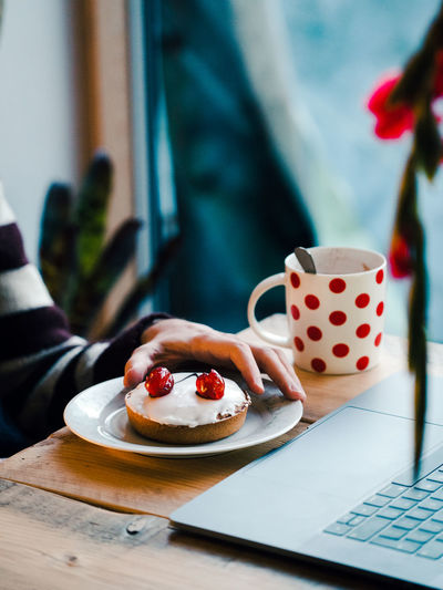 Midsection of a person with coffee cup, cherry tart and laptop on  a wooden table
