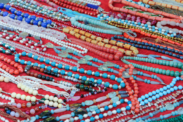 Necklaces for sale at a market stall in Rome, Italy Necklaces Sphere Art And Craft Backgrounds Business Choice Close-up Day For Sale Full Frame High Angle View In A Row Indoors  Jewellery Market Multi Colored Necklace No People Pattern Red Retail  Selection Still Life Textile Variation