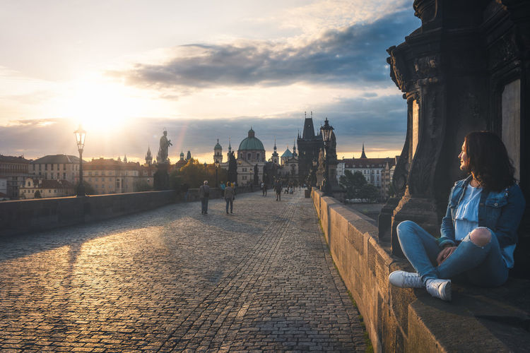 Woman sitting at charles bridge against sky during sunset