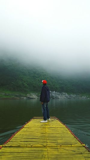 Full length of man standing on pier over lake