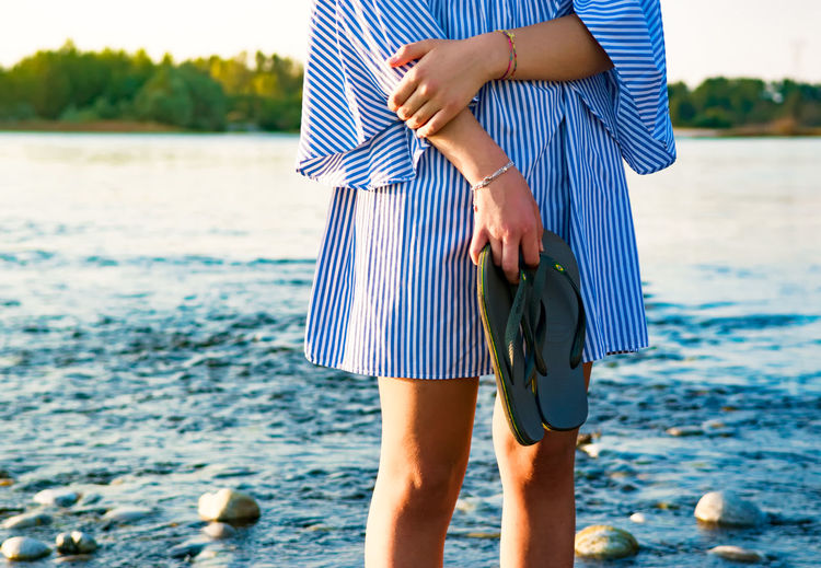 Midsection of woman holding footwear at beach