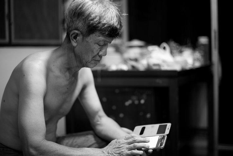 Shirtless senior man using phone while sitting at home