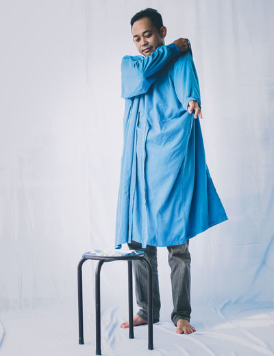 Full length of woman standing against blue wall
