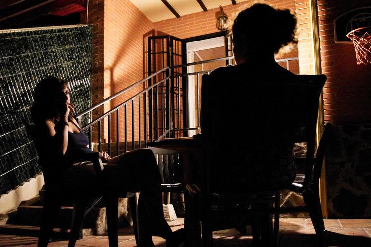 Rear view of two women talking at night Backyard Adult Chair Full Length Men Musical Instrument Night People Rear View Seat Sitting Social Issues Social Life Talking Two People Women Young Adult HUAWEI Photo Award: After Dark