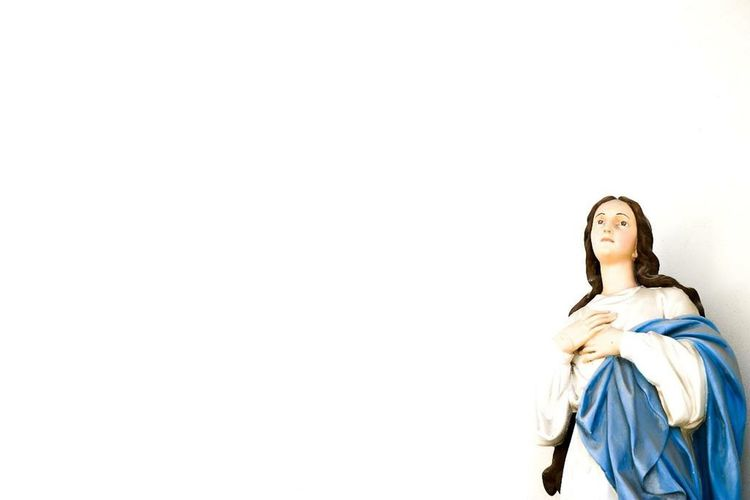 Low Angle View Of Virgin Mary Over White Background