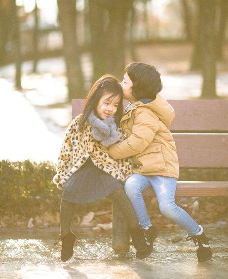 Children sitting on bench in winter