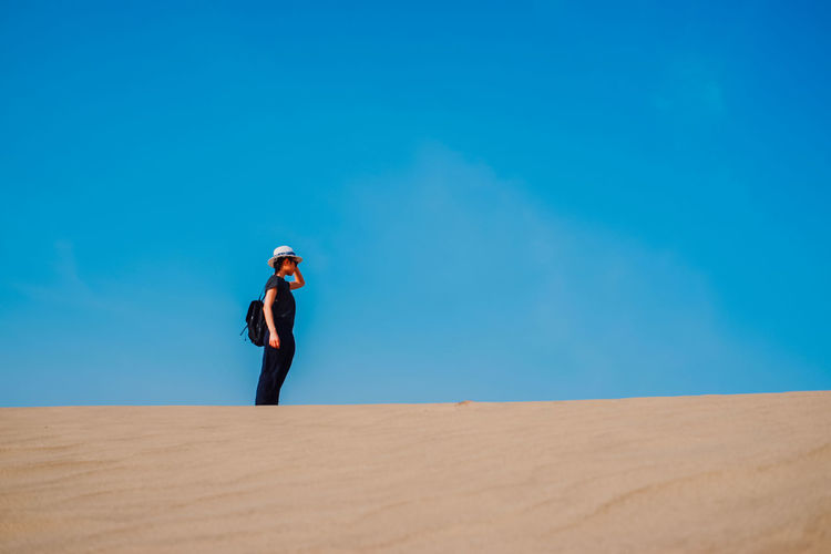 Woman Standing On Desert Against Blue Sky