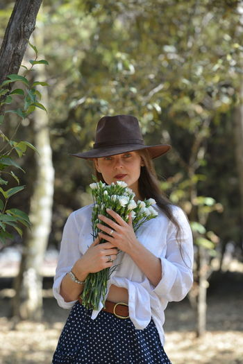 Portrait of beautiful woman holding flowers standing by trees