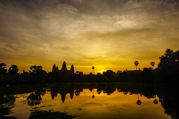 Sunrise over angkhor wat Angkor Wat, Cambodia Angkor Wat, Temples, Kmer Culture Ancient Civilization Architecture Beauty In Nature Building Exterior Built Structure Cloud - Sky Day History Lake Nature No People Outdoors Reflection Religion Scenics Silhouette Sky Spirituality Sun Sunset Travel Destinations Tree Water