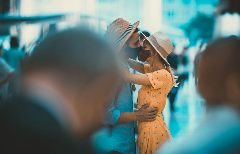 Side view of couple wearing mask kissing outdoors
