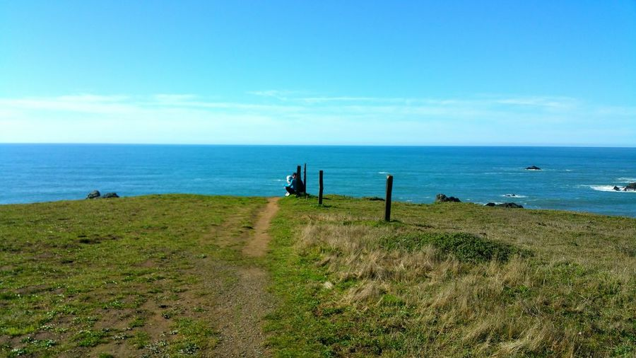 path to the cliffs edge. Real People Pathway Sitting Resting Zen Distance Silence Elegant Copy Space Rewilding Pathway Hiking Walking Path Horizon Over Water Fence Posts Rural EyeEm Selects Sea Horizon Over Water Beach Water Sky Nature Day Outdoors Scenics Tranquility Clear Sky Landscape An Eye For Travel Love Yourself