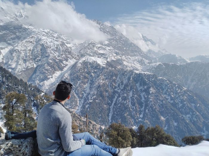Rear view of man sitting on snowcapped mountain