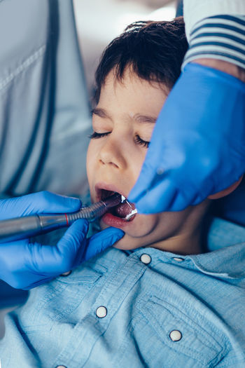 Cropped image of dentist examining boy at clinic