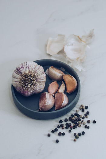 Garlic and Peppercorns on White Marble Cooking Herb Herbs PEPPERCORN Peppercorns Black Peppercorn Close-up Food Food And Drink Food Stories Freshness Garlic Garlic Bulb Garlic Clove Healthy Eating Indoors  Ingredient No People Pepper Spice Spices Still Life Table White Marble