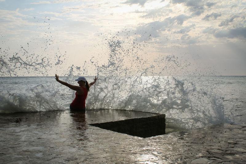 Wave Splashing On Woman At Sea Shore