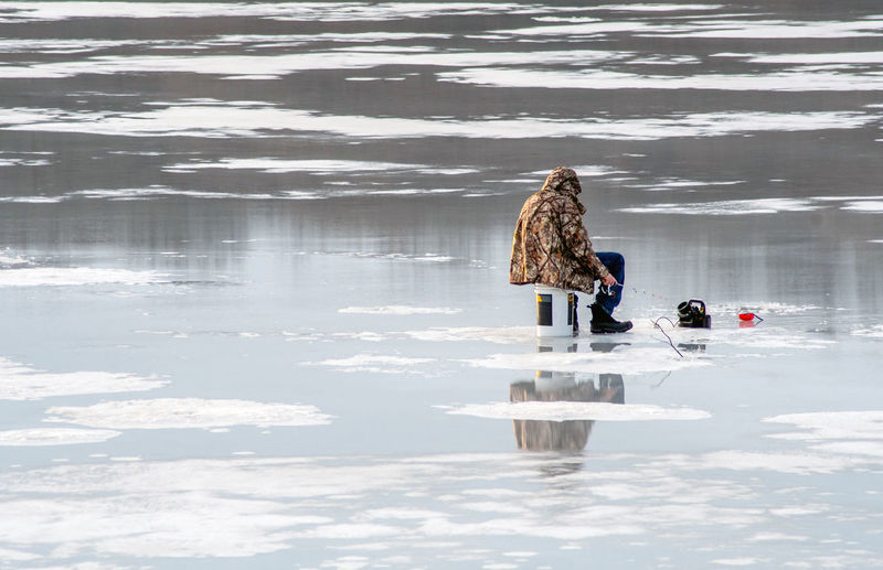 Woman walking on snow covered lake during winter