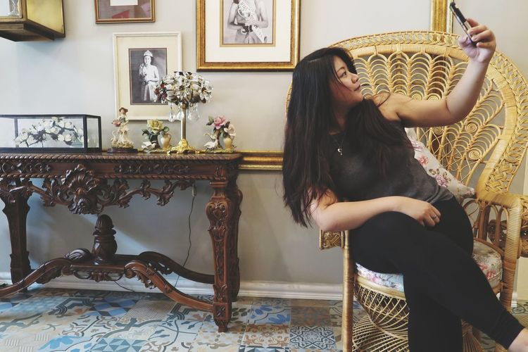 Young woman taking selfie on chair at home