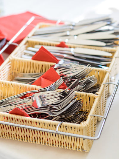 High angle view of forks and table knives in baskets on table