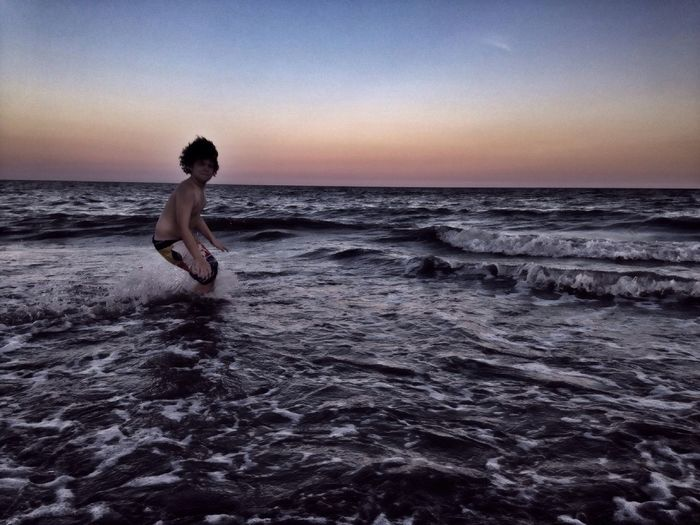 Shirtless boy standing in sea against sky during sunset