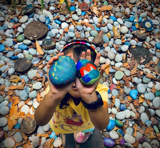 High angle view of boy playing with stones