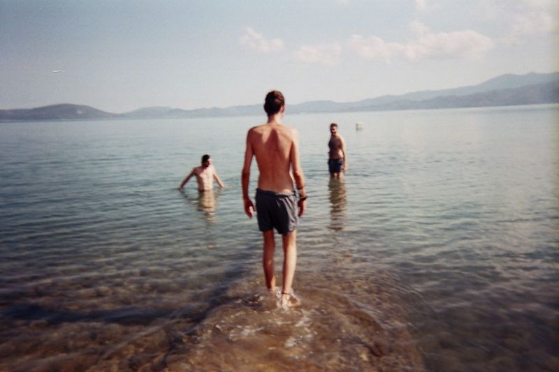 Rear view of friends on sea shore against sky