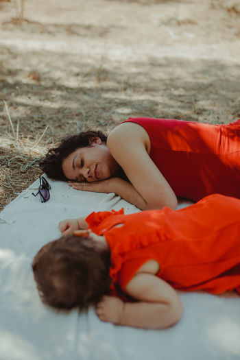 Woman sleeping with baby girl on picnic blanket at land