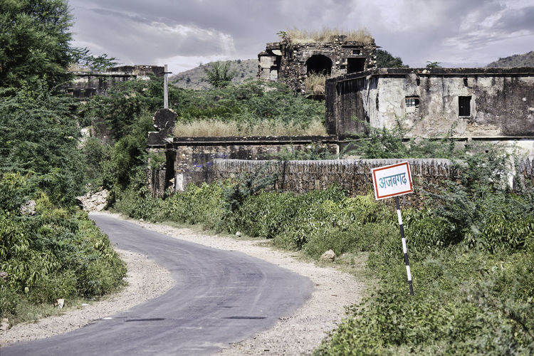 Road sign by trees against sky in city in bhangarh fort, rajasthan