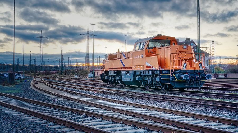 Train on railroad tracks against sky during sunset