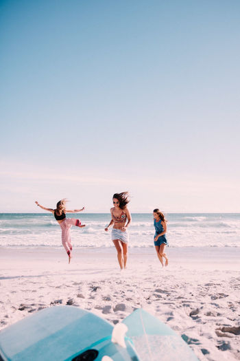 Playful Female Friends Playing At Beach
