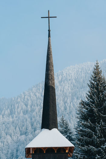 Church by trees in forest during winter