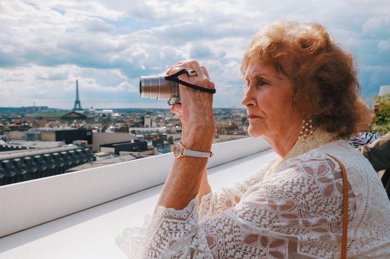 Mid adult woman against built structure against sky