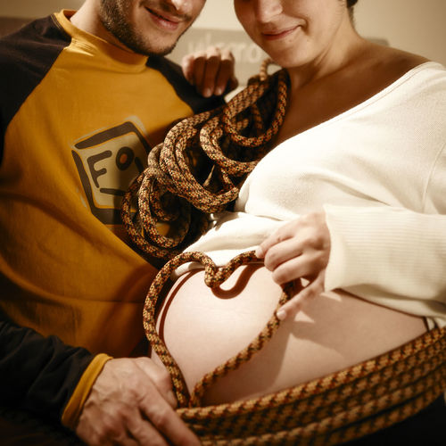 Midsection of couple making heart shape with rope on pregnant woman abdomen