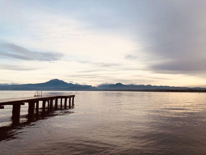 Pier over lake against sky