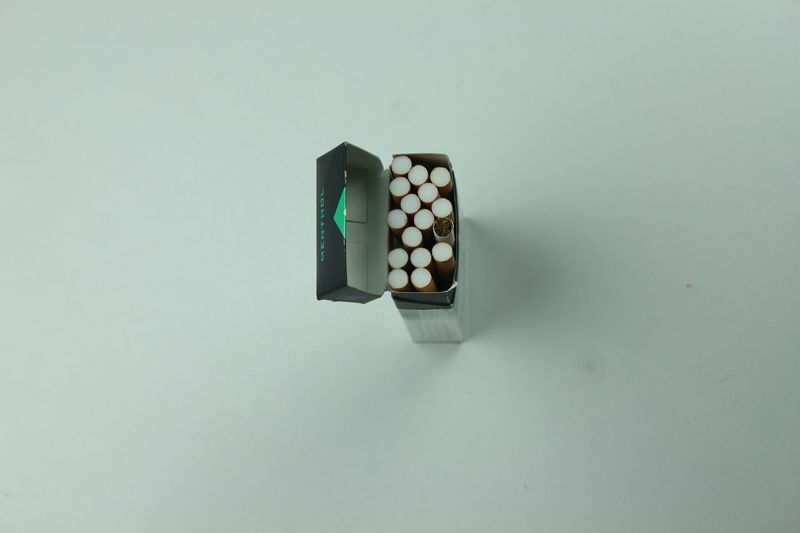 High angle view of Open packet of cigarettes Flaylay Menthol  Cigarettes EyeEm Selects Copy Space Indoors  Still Life Directly Above No People Studio Shot Table Container Green Color High Angle View Healthcare And Medicine Close-up Pattern
