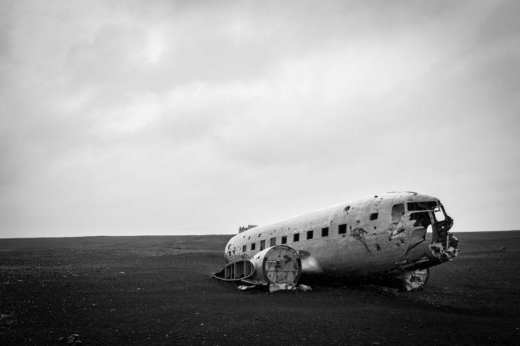 Abandoned airplane on runway against sky