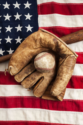 Vintage baseball, bat and glove on a vintage American flag American American Flag Antique Baseball Bat Old Fashioned Past Time Retro Ball Baseball - Sport Baseball Bat Baseball Glove Equipment Flag High Angle View No People Patriotism Sports Vintage