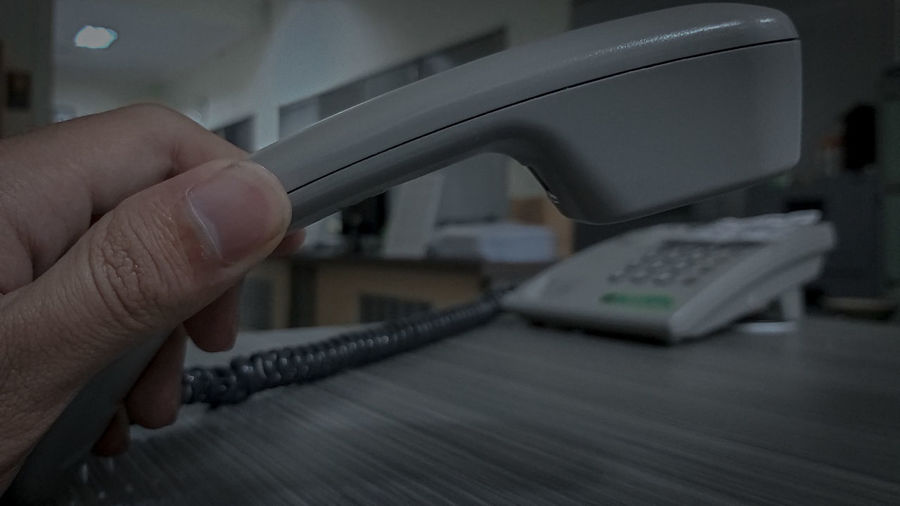 Close-up of man holding landline phone at office desk