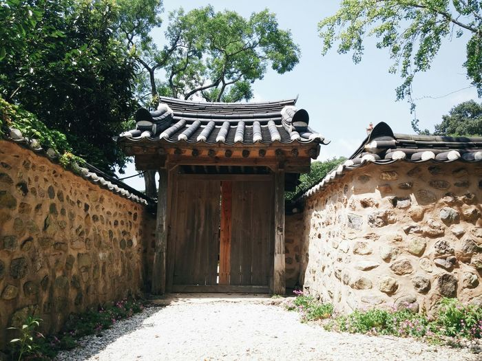 A traditional korean architecture. A small wooden door eith mud walls.